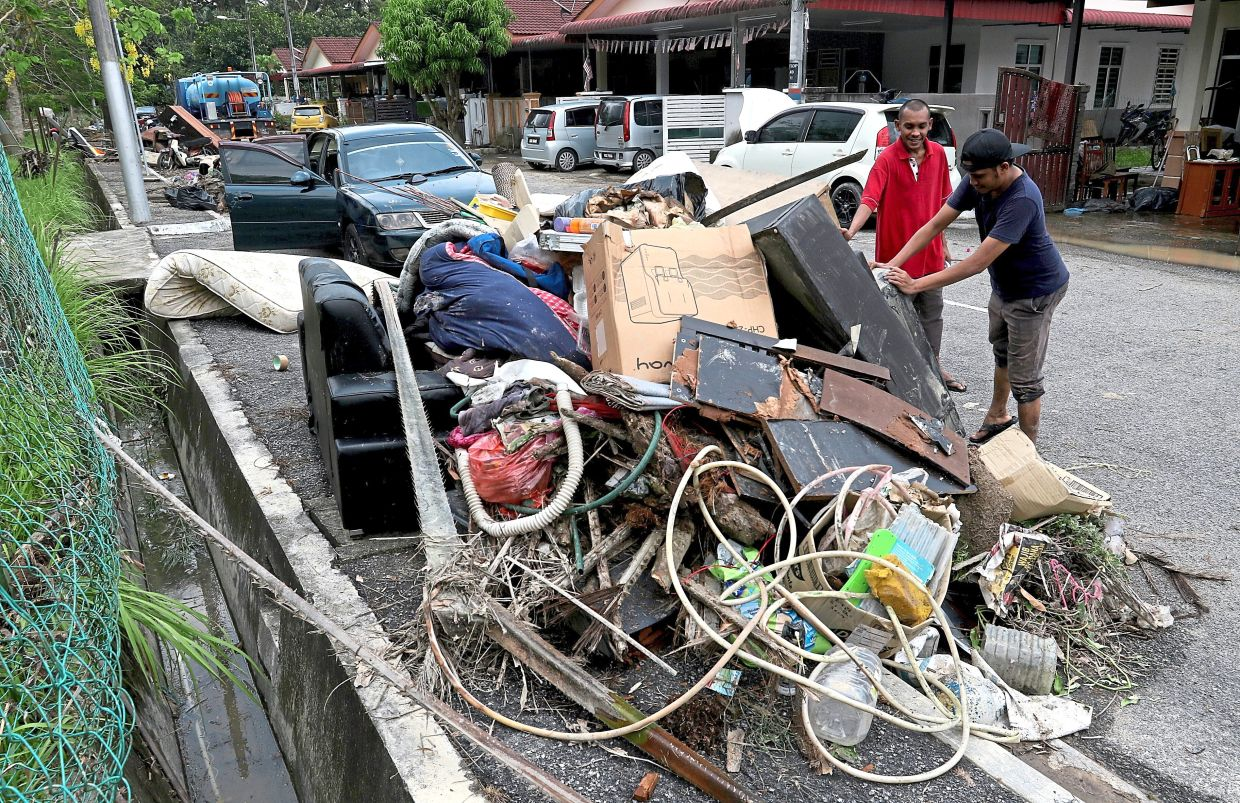 Residents throwing away belongings that were destroyed in the floods.