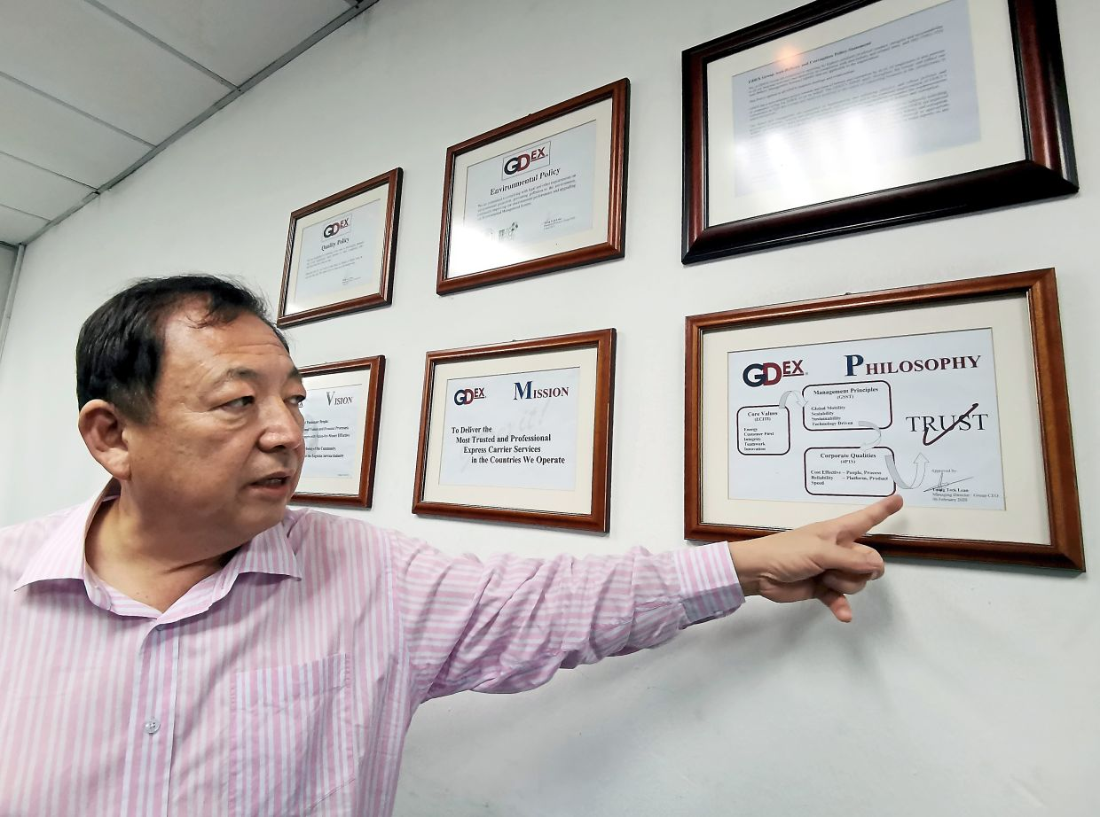 GDex managing director and group CEO Teong Teck Lean points out the new philosophy framed up in GDex\'s headquarters.