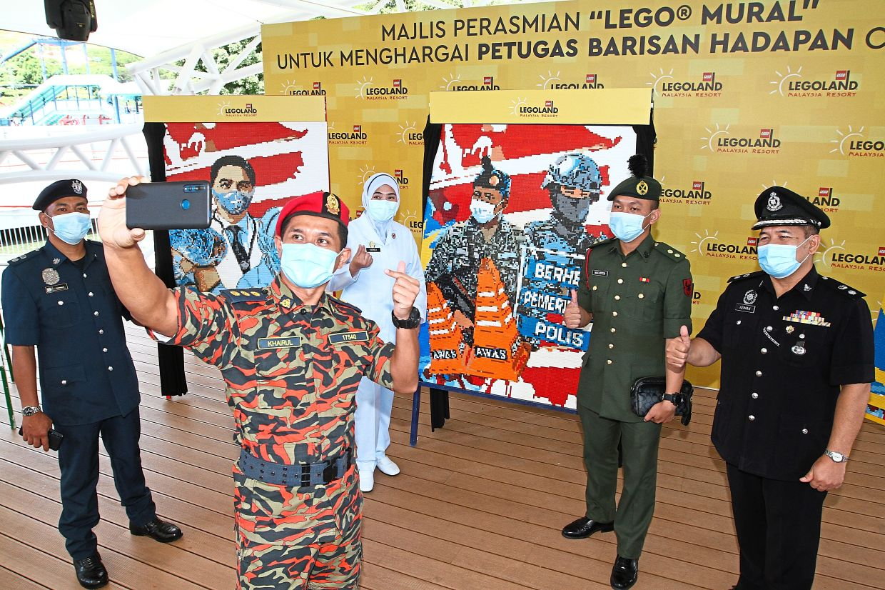 Tribute to the heroes: Frontliners taking a wefie in front of the Lego murals at Legoland Malaysia Resort. — THOMAS YONG/The Star
