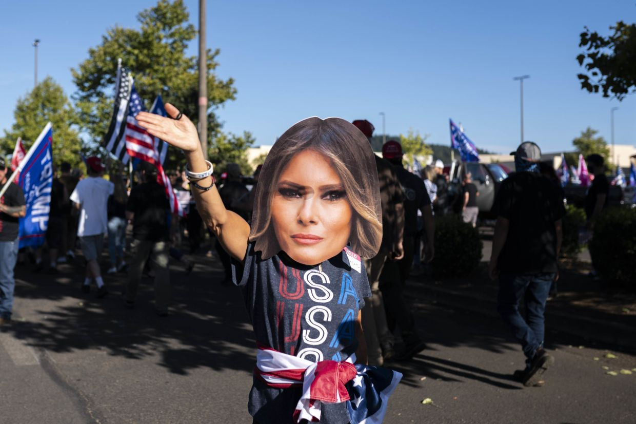 A supporter of President Trump wears a mask of the first lady at a rally in Portland last month.  — AFP