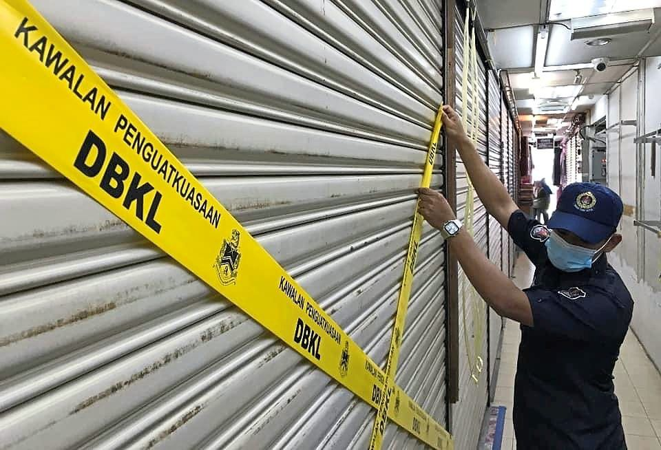 A DBKL enforcement officer sealing a business premises illegally run by undocumented foreigners. — Filepic