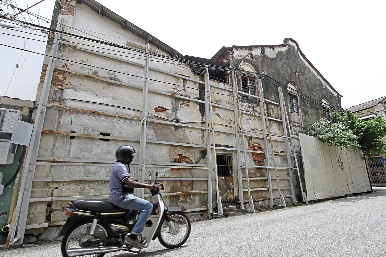 The dilapidated building supported by metal frames is located at the Love Lane-Muntri Street junction in George Town.