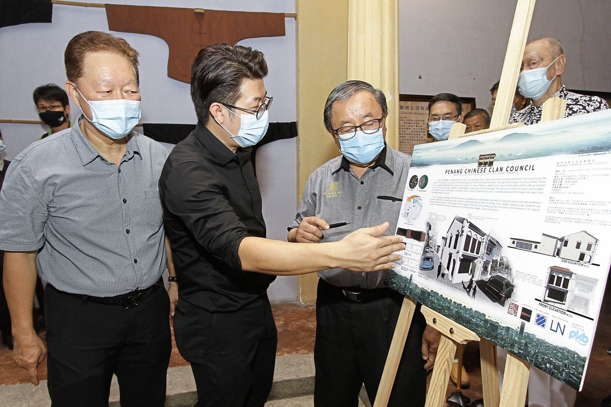 (From right) Perunding YAA Sdn Bhd owner Datuk Yap Ching Chau, Ooi and Yeap looking at an artist's impression of the restored Love Lane building.