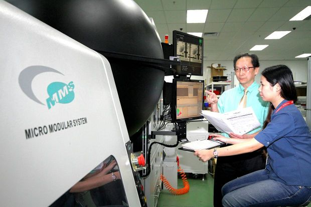 MMS chief executive officer T.K. Sia checking out a test equipment with an employee.