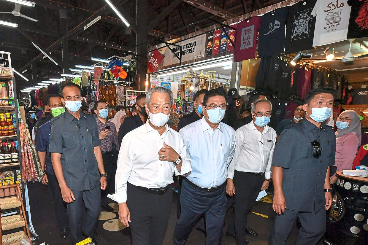 Meeting the people: Muhyiddin (second from left) visiting the Pahlawan Walk bazaar where he met the public and bought some dodol. With him is Sulaiman (third from right). — Bernama