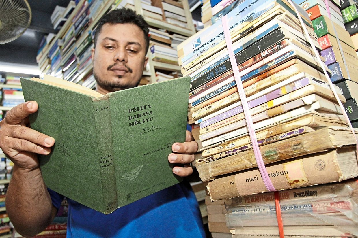Mohamed Assalam browsing through a classic Malay book at his second-hand bookstore.
