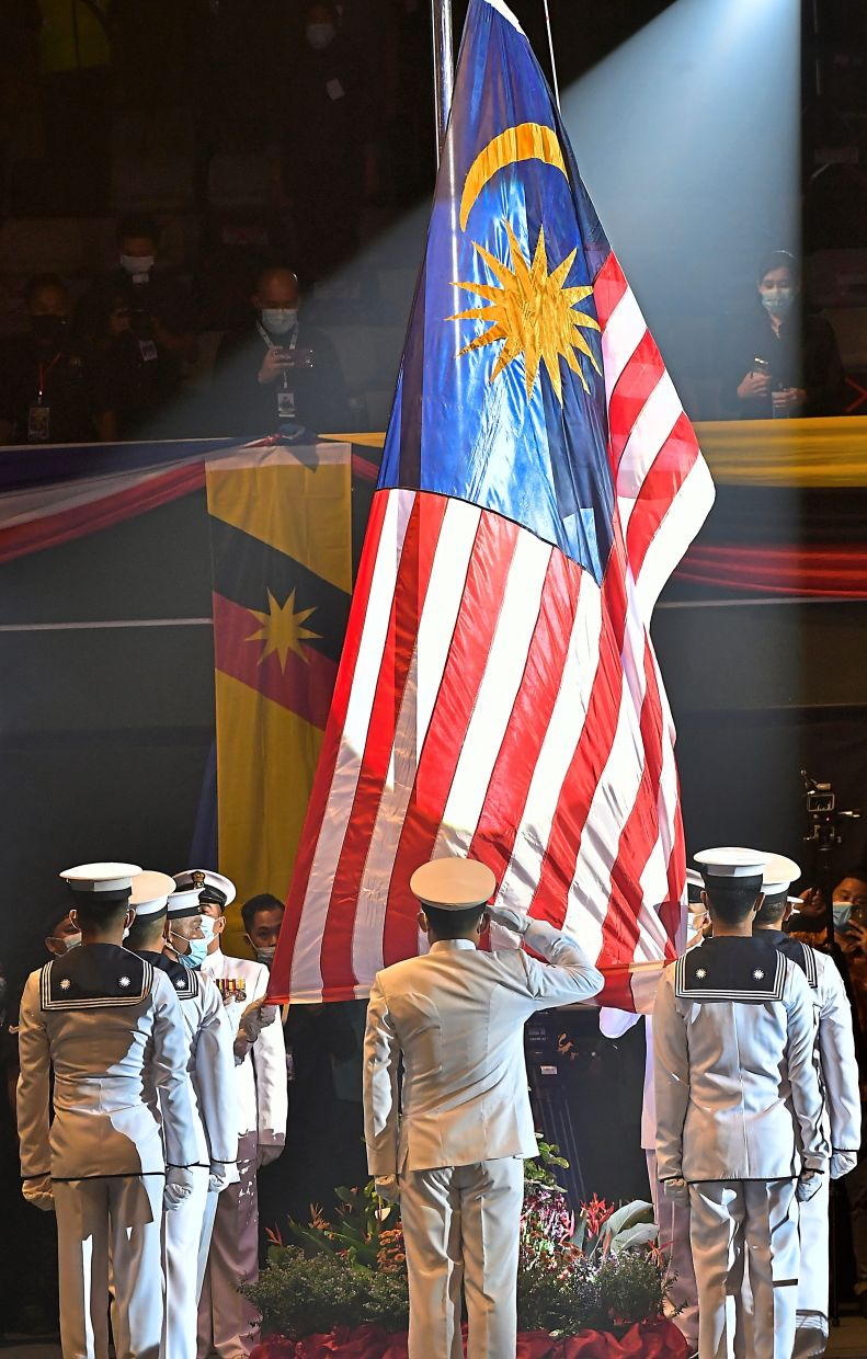 Standing united: Royal Malaysian Navy raising the Jalur Gemilang at the Sibu indoor stadium in conjunction with the Malaysia Day celebration. — Bernama