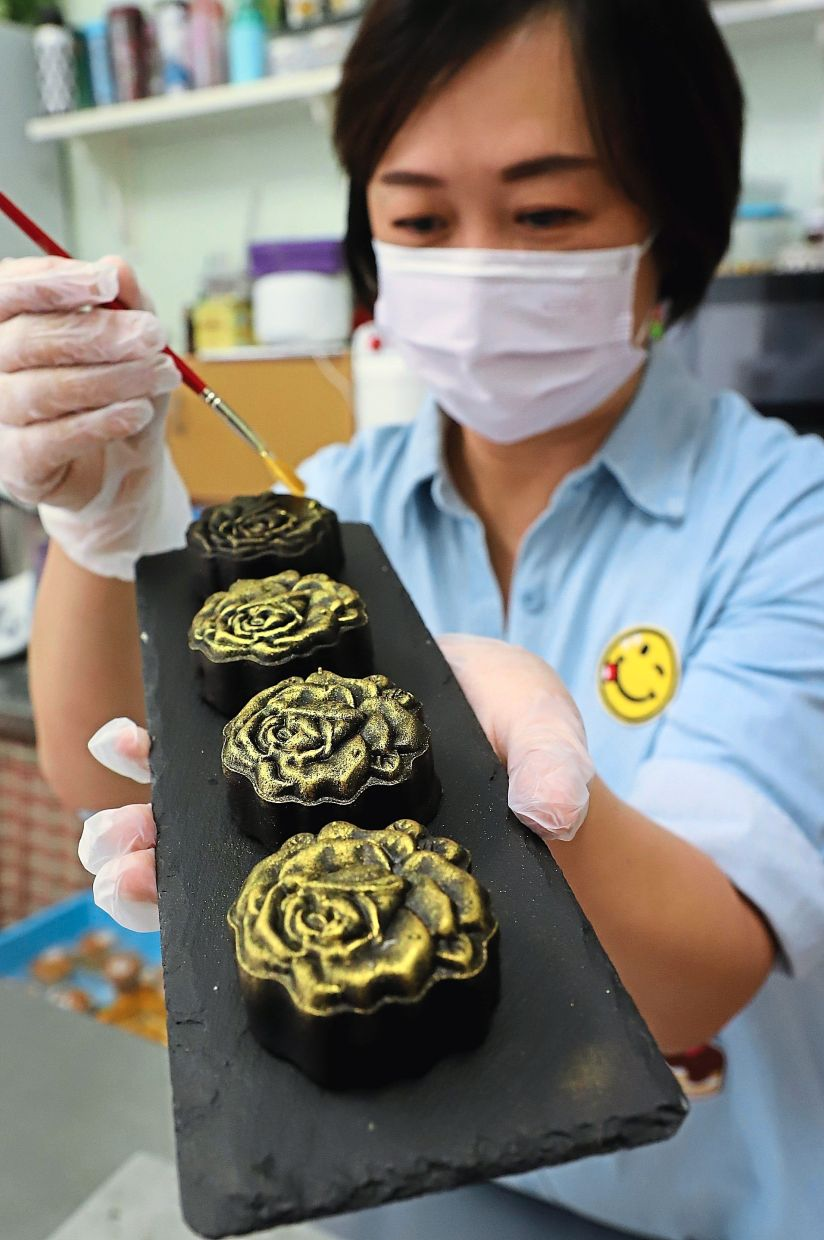 Going for gold:  Teow  dusting her mooncakes in gold glitter at her shop in Bayan Baru, Penang. — LIM BENG TATT/The Star