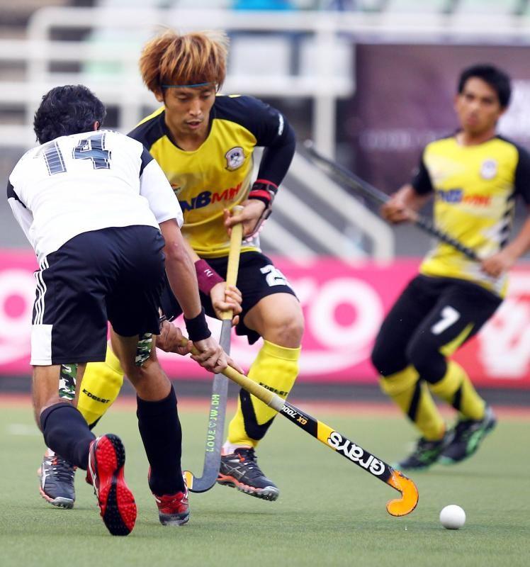 Terangganu's Jang Jong Hyun (right) and Maybank 's Shakeel Abassi (left) fight for the ball during their second league semi final match at Stadium hockey Bukit Jalili on Dec 12, 2014. AZHAR MAHFOF/The Star