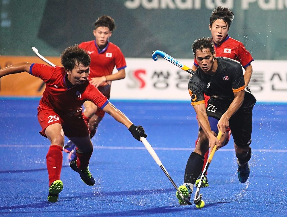 Malaysia's Muhammad Shahril Saabah (right) control the ball from Japan's Zendana Hirotaka (left) in Hockey Field Gelora Bung Karno during Asian Games 2018 at Jakarta, Indonesia. FAIHAN GHANI/The Star.