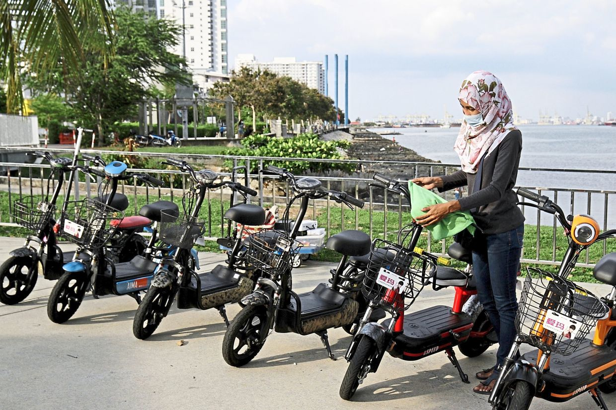 An e-scooter operator cleaning the vehicles for rental there.