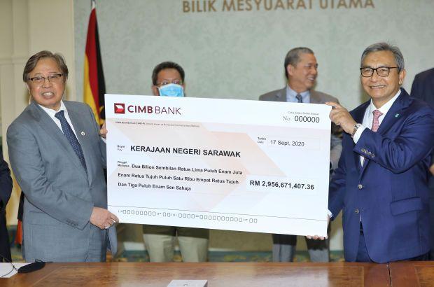 Petronas chairman Tan Sri Ahmad Nizam Salleh (right) handing over the mock cheque for state sales tax to Chief Minister Datuk Patinggi Abang Johari Tun Openg.