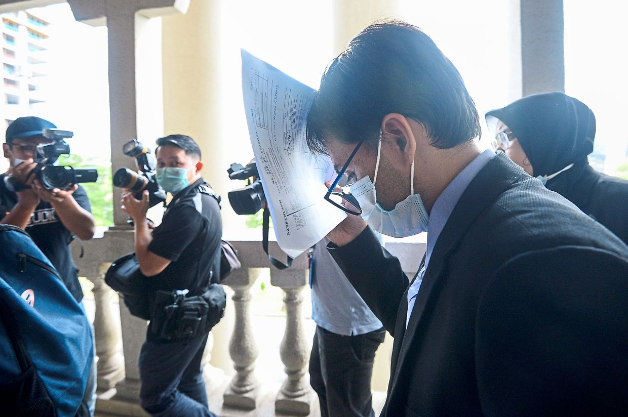 Facing the law: Wafiy covering his face as he enters the Kuala Lumpur Sessions Court.