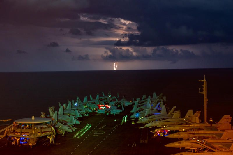 Lightning flashes over the US Navy aircraft carrier USS Nimitz as it transits the South China Sea on July 4, 2020. - Reuters