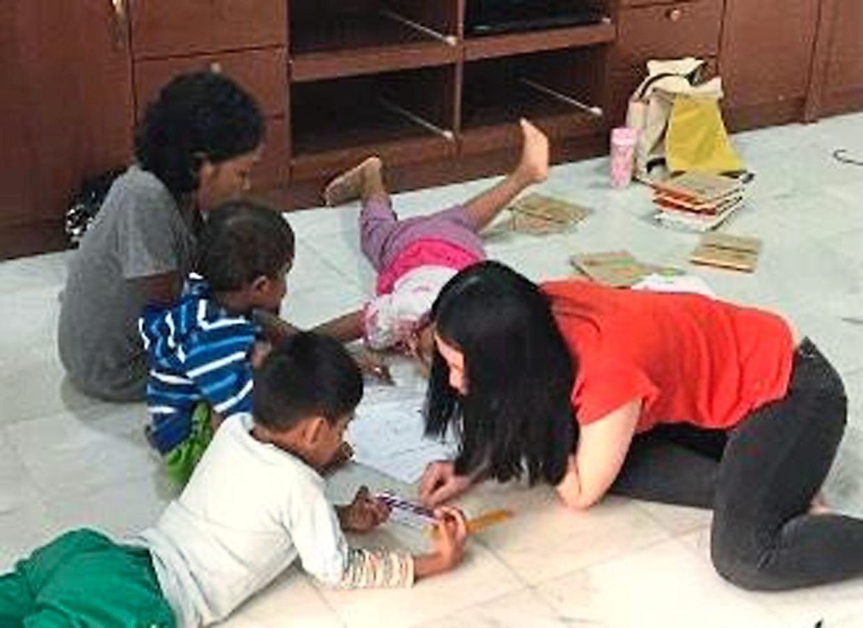 Let's learn: Jia Suan (right) teaching English to Orang Asli children.