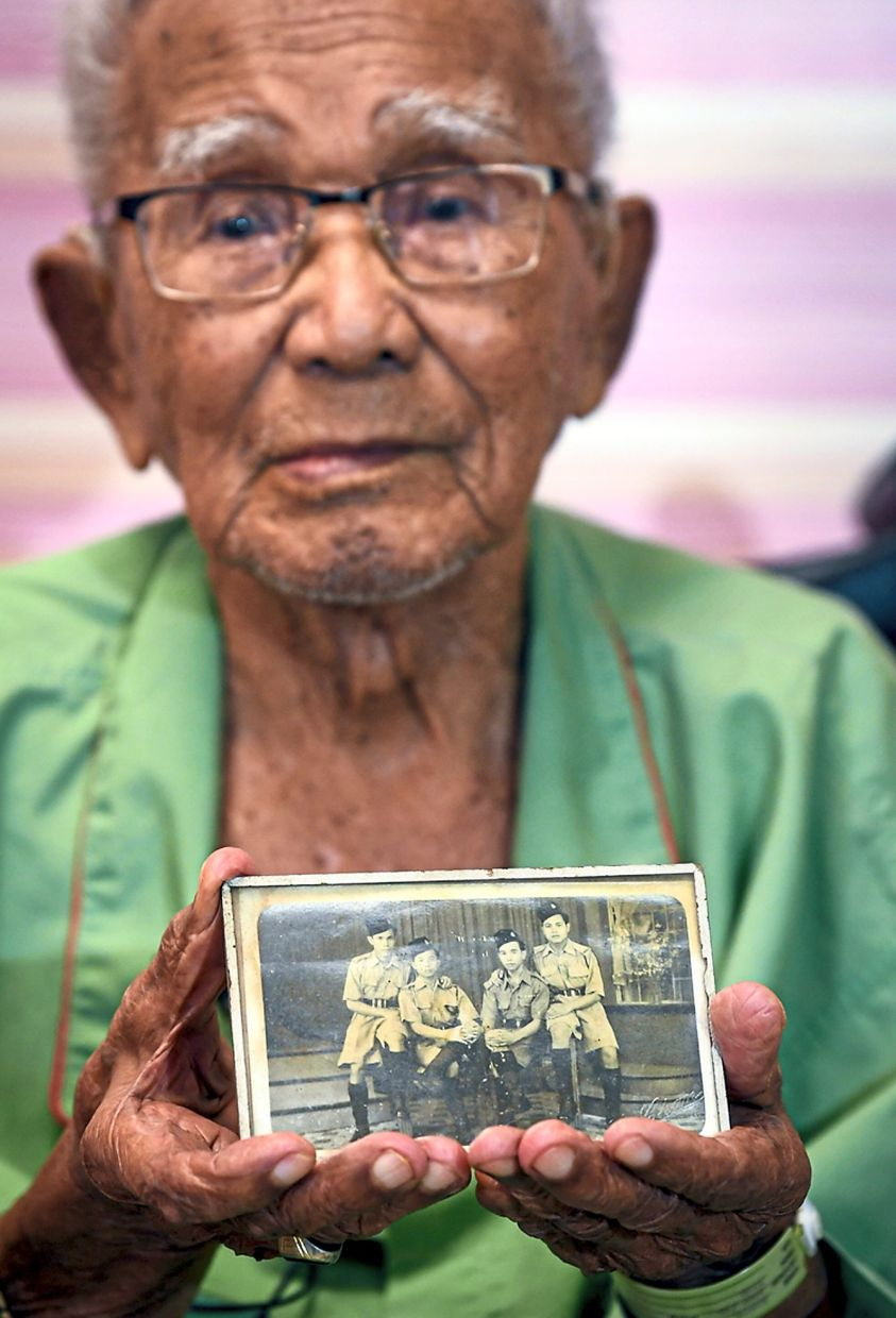 Band of brothers: Ujang showing a picture of him and his comrades in the army. — Bernama