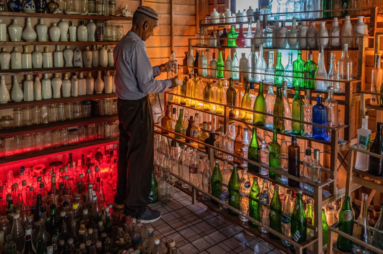 Tengku Mohamad Ali Mansor inspecting a glass bottle at his bottle museum. Photo: AFP