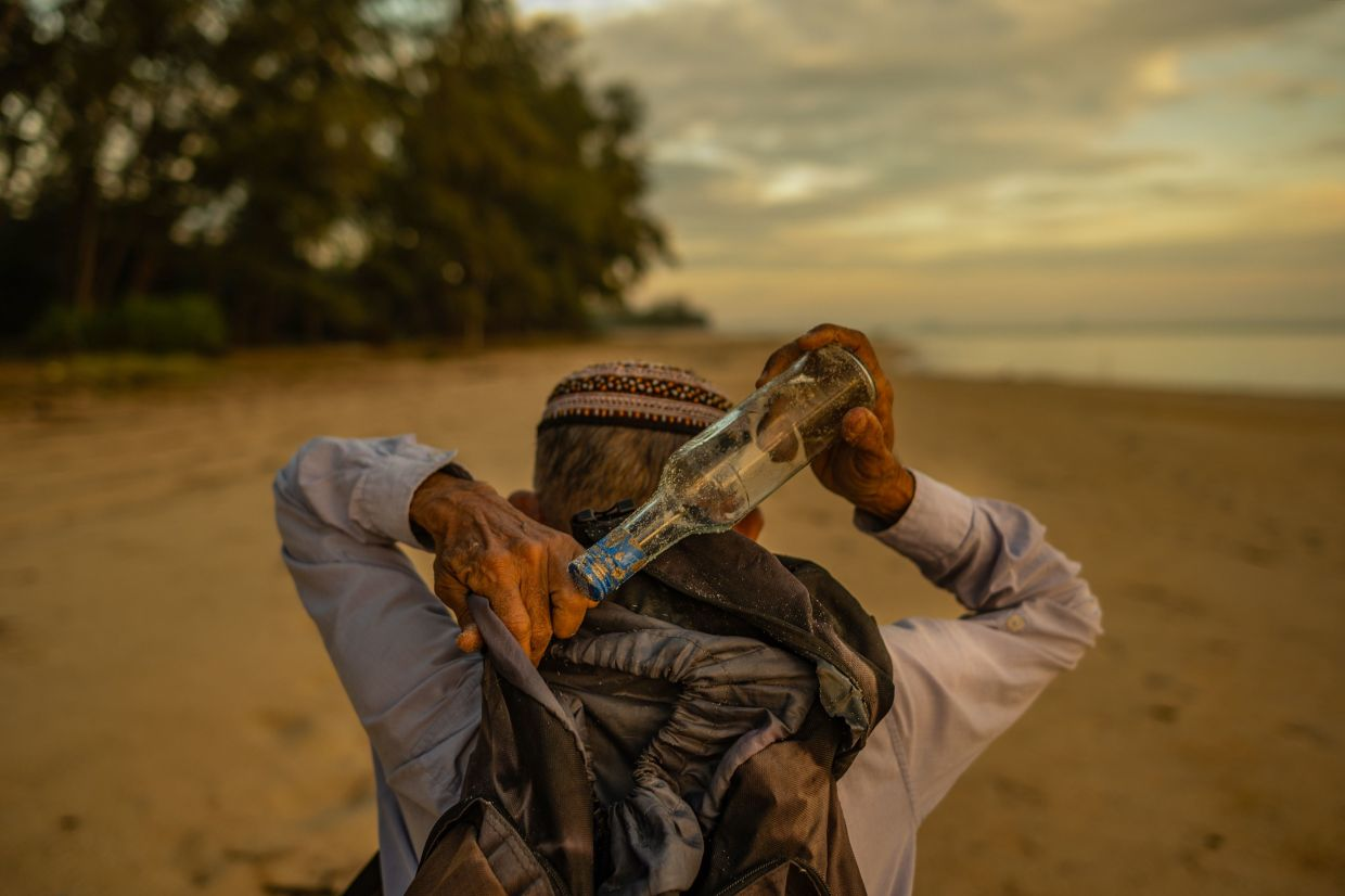 Tengku Mohamad Ali Mansor keeping a glass bottle he found on the beach in his backpack during sunrise at a beach in Mangkuk village in the Setiu district of Terengganu. Photo: AFP