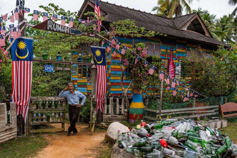 Tengku Mohamad Ali Mansor posing for pictures outside his bottle museum in Penarik village in the Setiu district in Terengganu. Photo: AFP