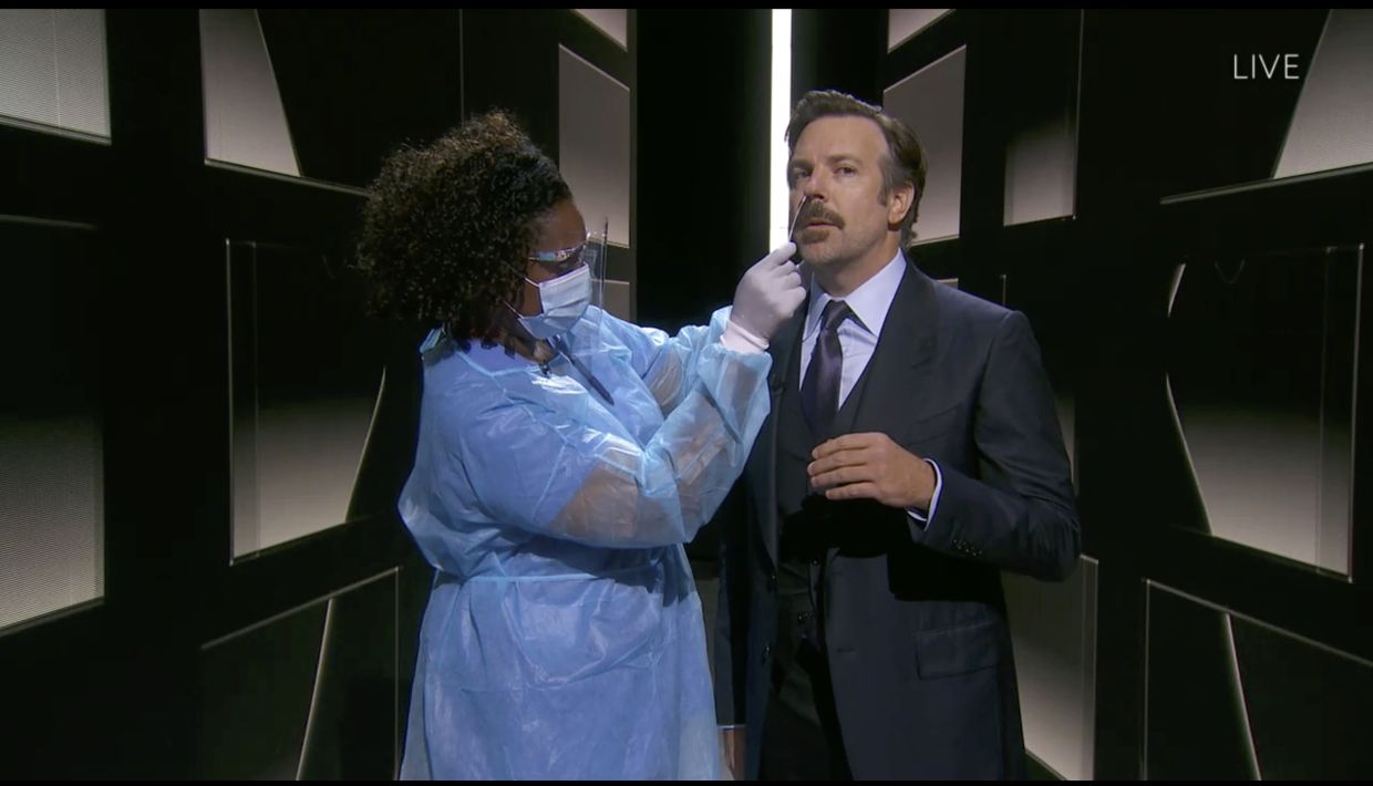 Nicole Butler taking a nasal swab from actor Jason Sudeikis during the 72nd Primetime Emmy Awards ceremony
