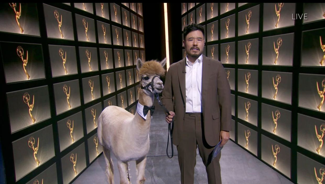 Actor Randall Park walking with an alpaca during the 72nd Primetime Emmy Awards ceremony.