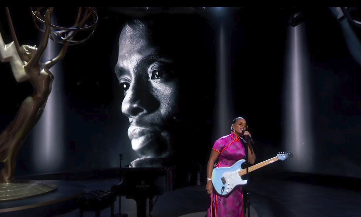 H.E.R. performs 'Nothing Compares 2 U' during an In Memoriam tribute as the late actor Chadwick Boseman appears on screen.