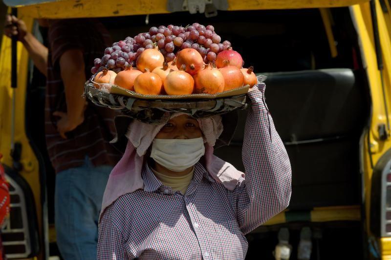 A vendor carries fruits for sale in Phnom Penh. - AFP