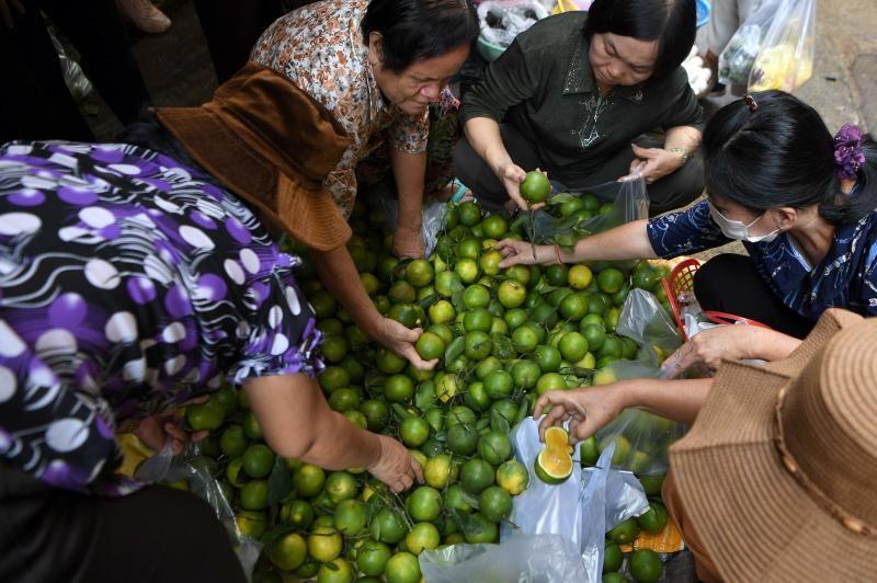 Women buying oranges at a market in Phnom Penh. - AFP