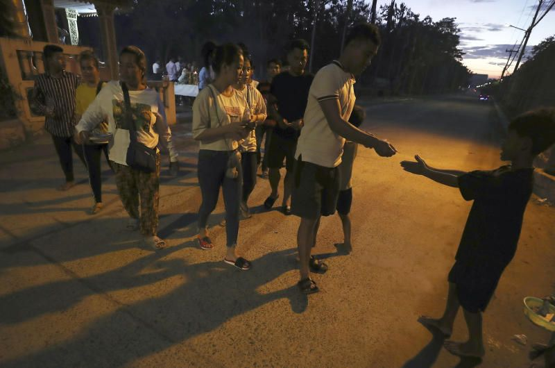 People donating money to a boy (right), as they make offerings during Pchum Ben (Ancestors' Day) at a Buddhist pagoda of Saroang Andet on the outskirt of Phnom Penh, Cambodia. - AP