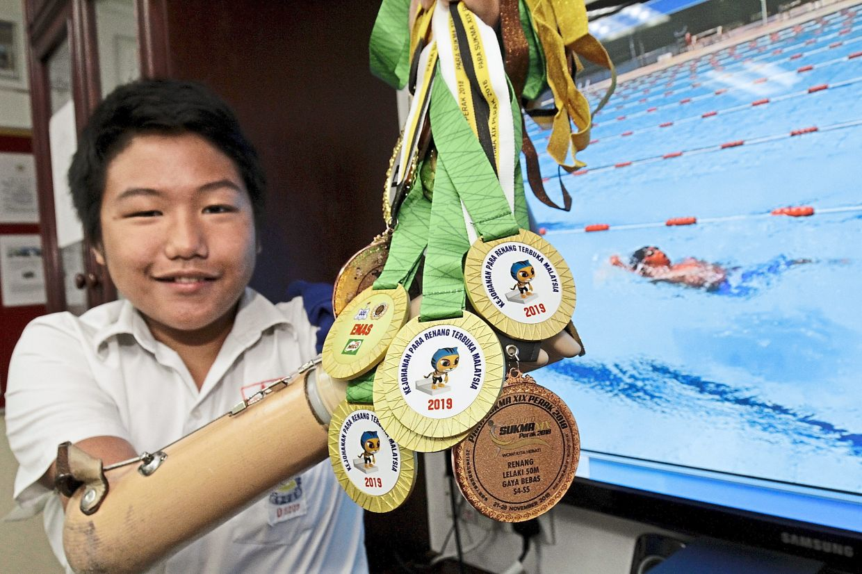 Kher Lee showing the medals he won at swimming meets.