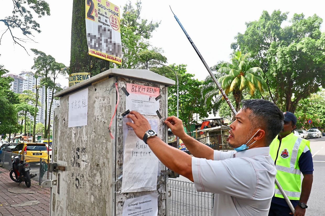 Ahmad removing advertisements placed illegally on an  electricity feeder pillar in Wangsa Maju.