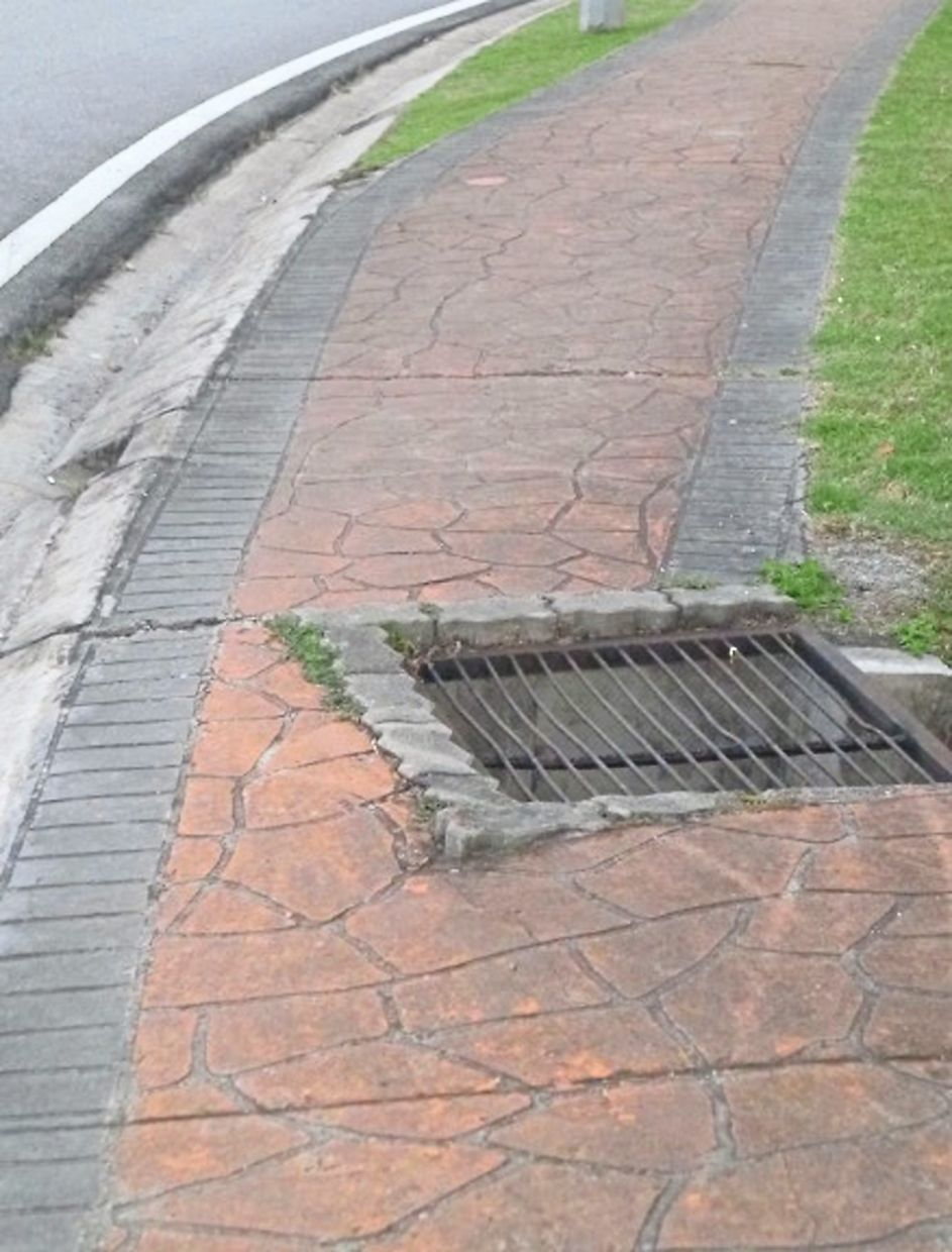 Example of a roadside pathway that is 'interrupted' by a drain cover.