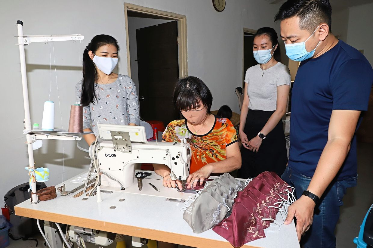 (Standing from right) Law, Penang Green Council senior officer Carmen Wong and its officer Kee Shin Ai watching Ang sew the cloth face masks at her home in Taman Bagan Jaya in Butterworth.