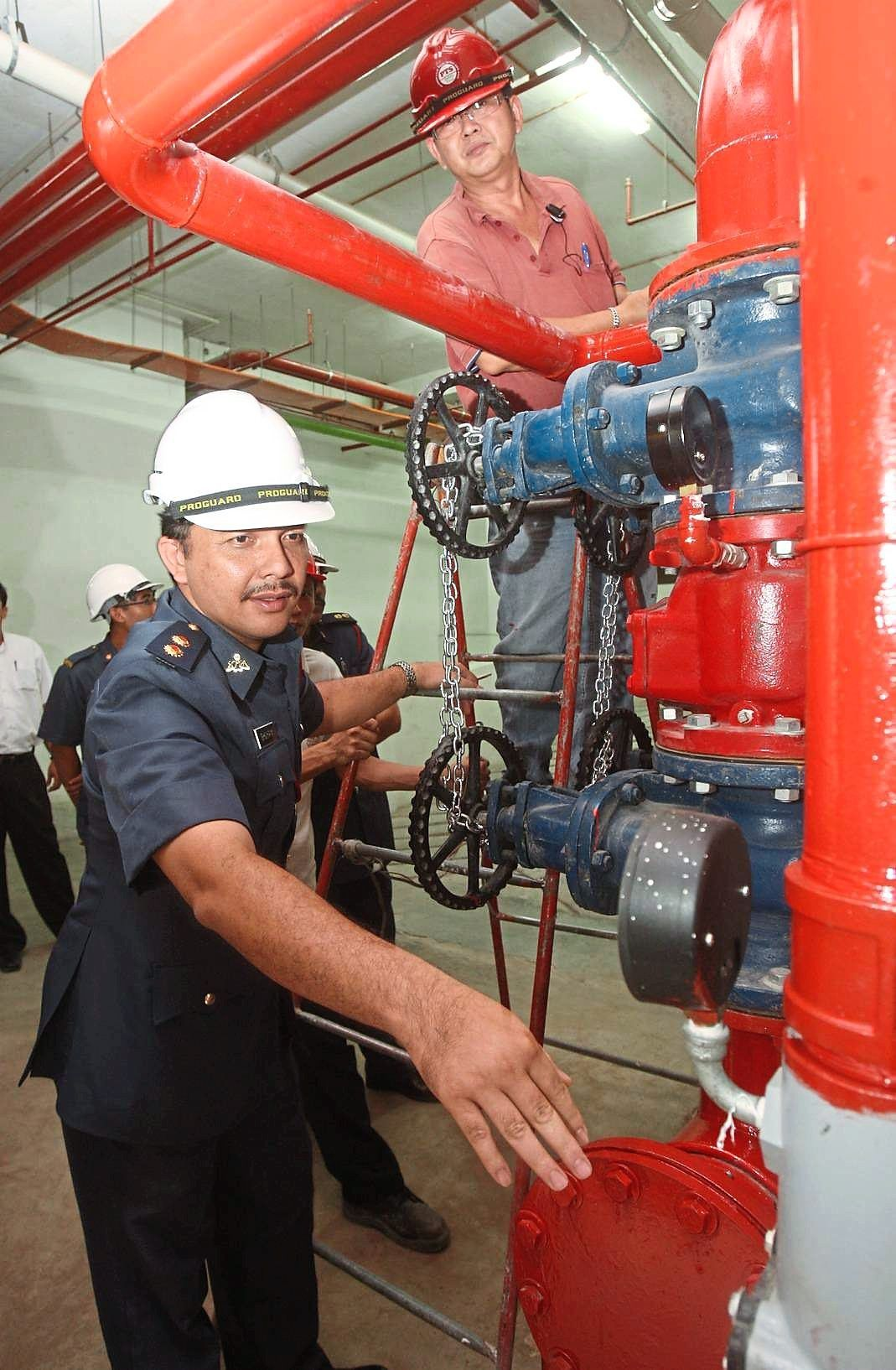 A Fire and Rescue Department enforcement officer checking a pressure gauge during a fire safety  inspection.