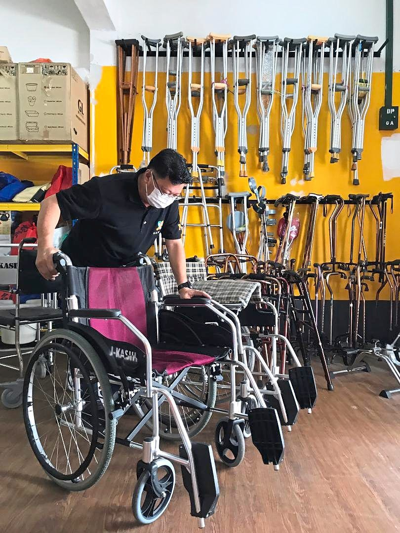 Wong checking the condition of wheelchairs at the centre before letting those in need borrow the equipment for free.