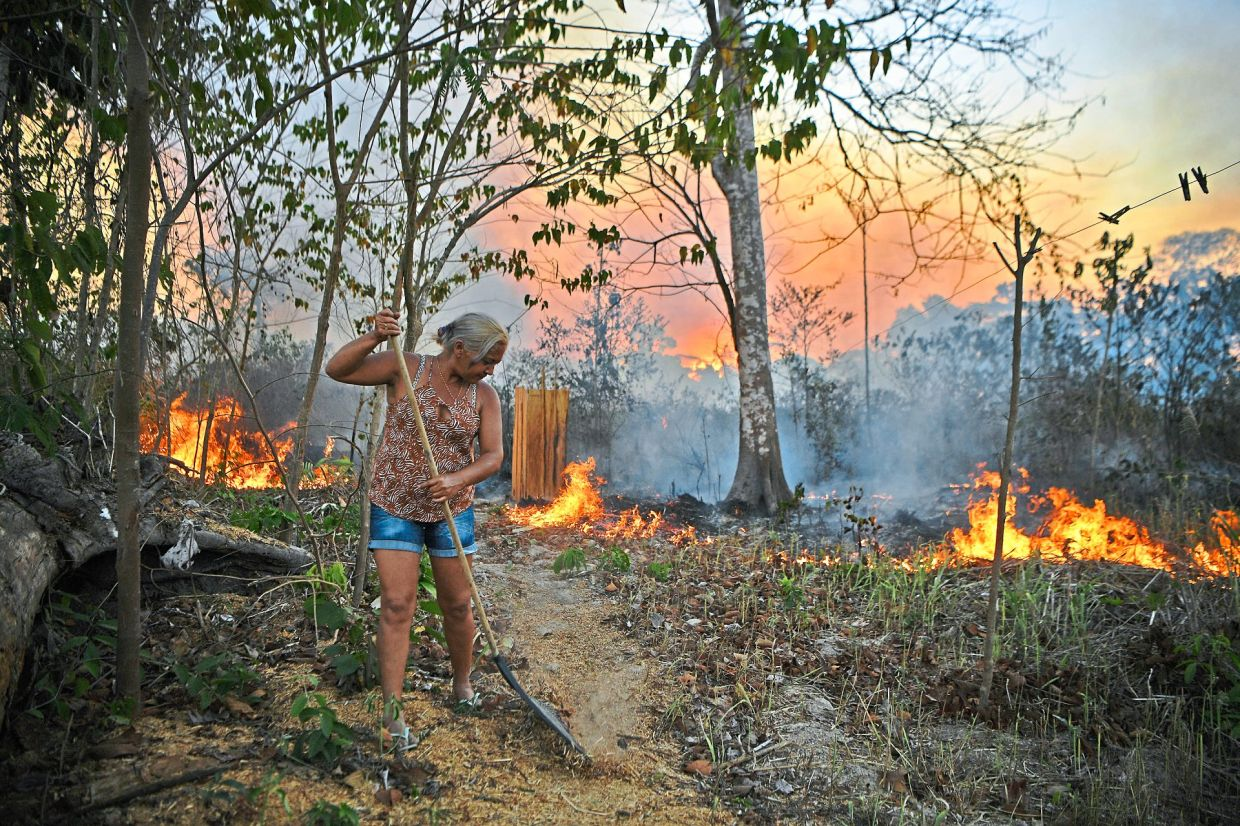 Idelia Lima Lisboa, wife of a farmer who set fire to rainforest around his property, tries to clear a path of dry leaves as the fire approaches their house in an area of Amazon rainforest in the Para state, Brazil, in August.