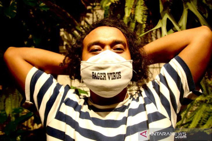 Muhammad Adimaja, a photojournalist working for ANTARA news agency, in Jakarta, wearing a custom face mask with a stencil writing: