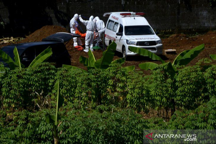 Health workers wearing full protective gears take out the body of a Covid-19 deceased from an ambulance at a Macanda cemetery in Somba Opu, Gowa, Makassar, South Sulawesi Province. — Abriawan Abhe/ANTARA