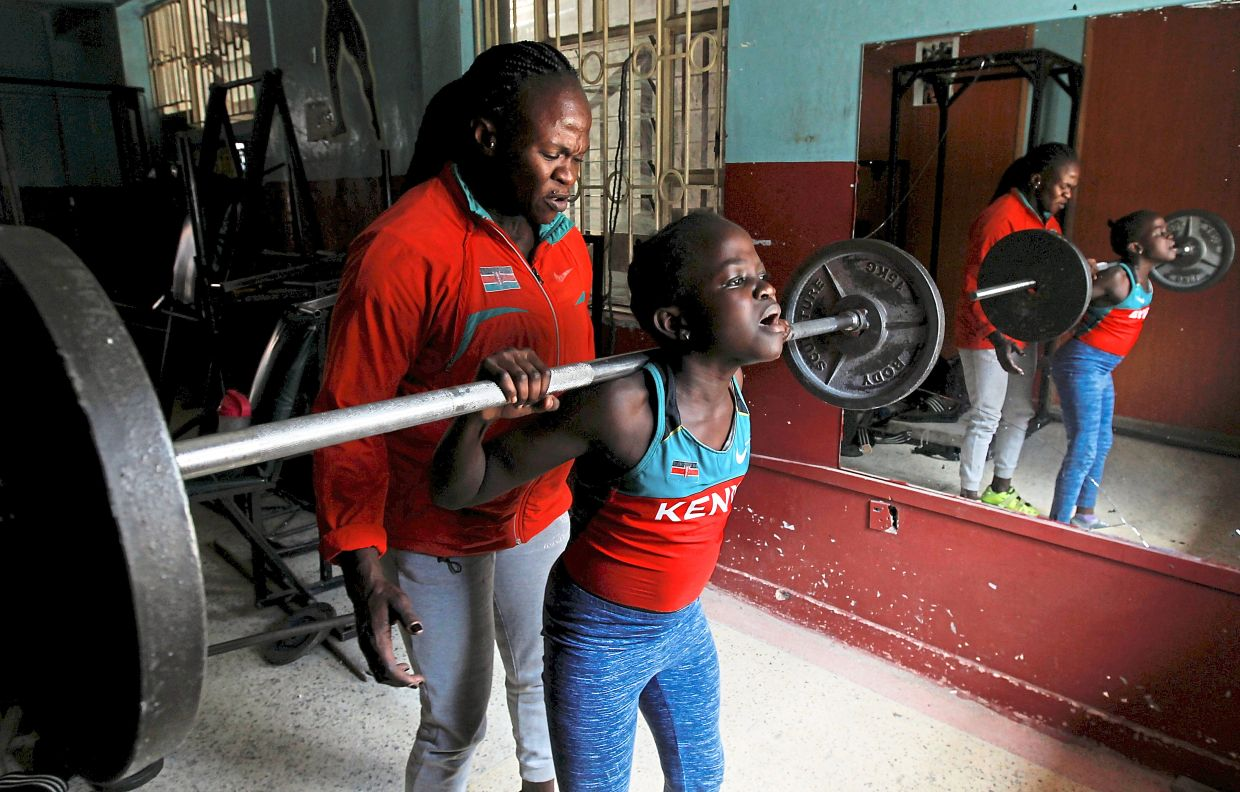 Obiero teaches her daughter Chanel how to lift weights during a training session. Photo: Reuters