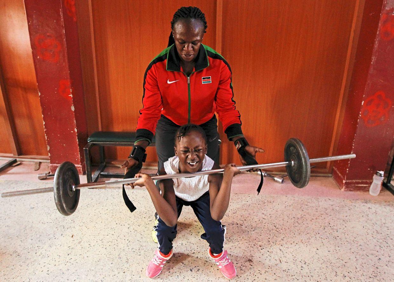 Keysha Atiky learns how to lift weights from her grandmother Obiero. Photo: Reuters/Monicah Mwangi