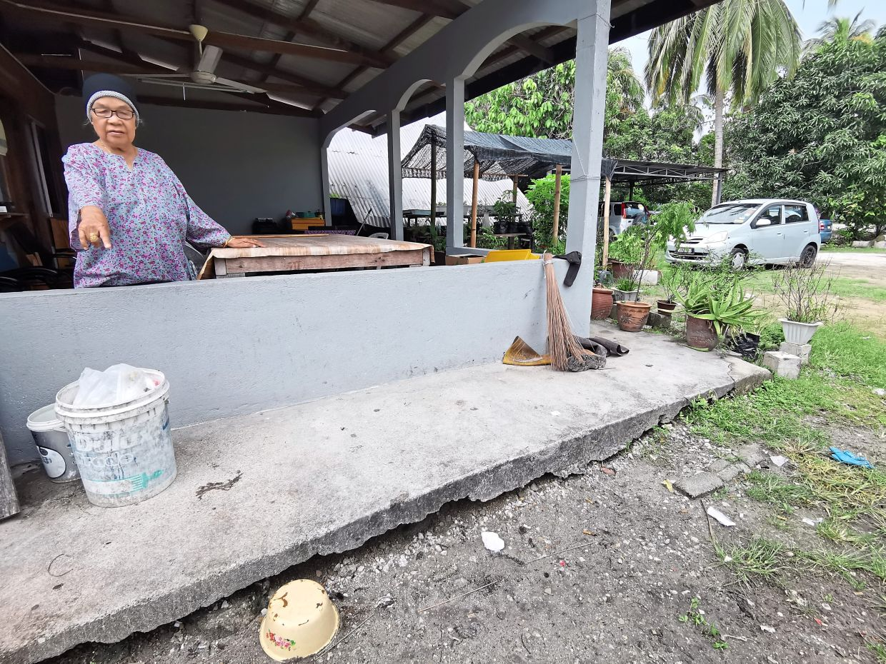 Yusof's mother, Jamillah Aishah Abdul, showing where flood waters have come right up to the side of their house in the past.