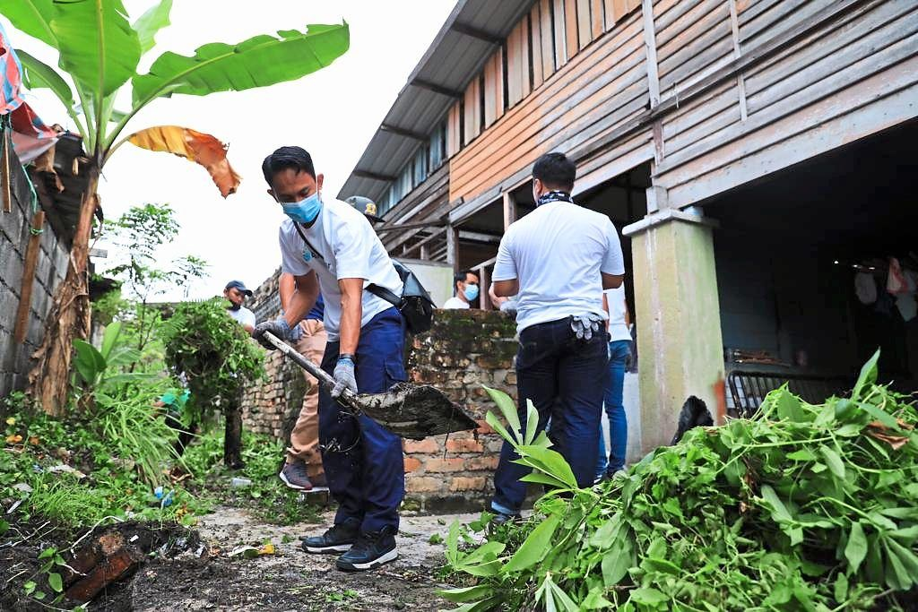 Air Selangor employees from the company's headquarters and Gombak office cleaning a villager's house in Kampung Selayang Baru.
