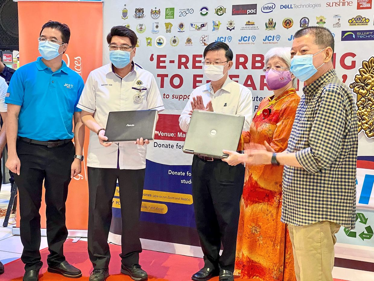 Chow (middle) witnessing the presentation of laptops from Yeoh (second left) to Chong Eng (in orange) at Sunshine Square in Bayan Baru, Penang.