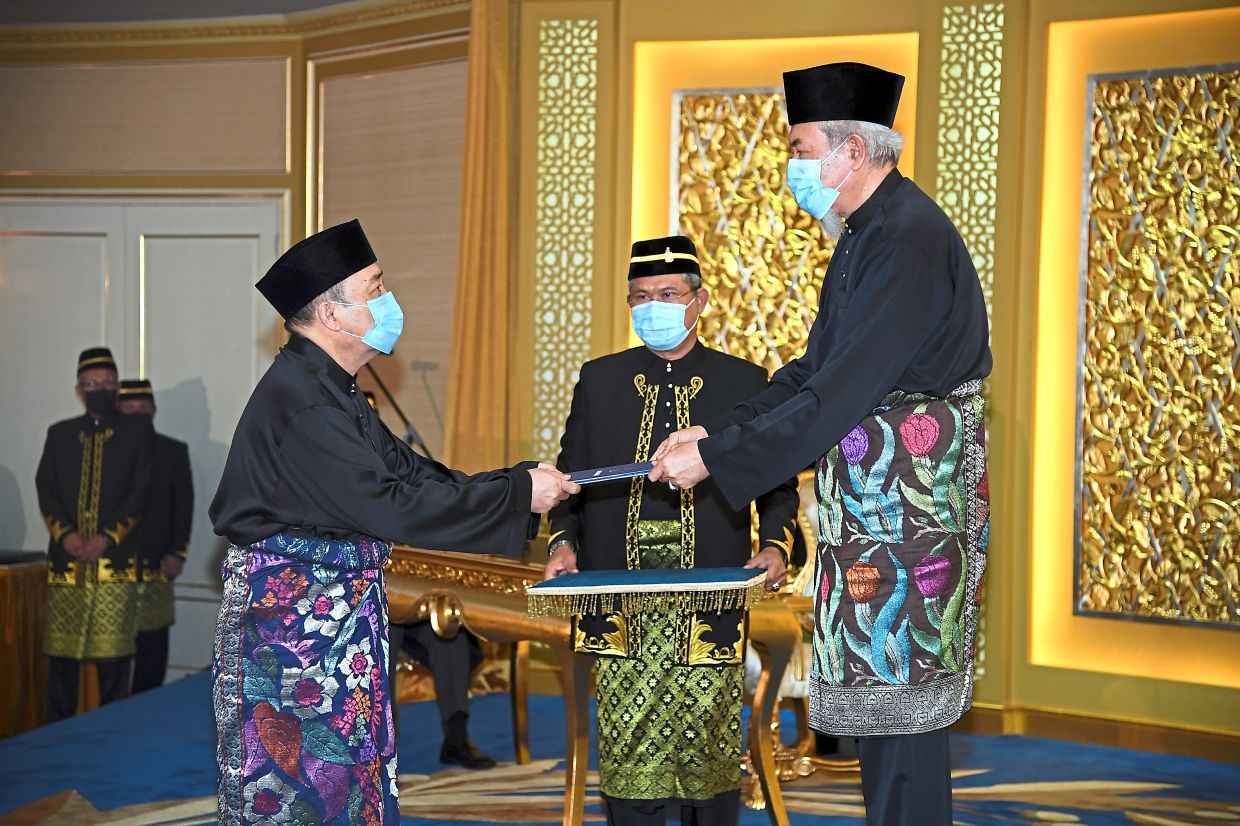 New chapter begins: Juhar presenting the letter of appointment to Hajiji at his swearing-in ceremony at the Istana Negeri in Kota Kinabalu. — Bernama