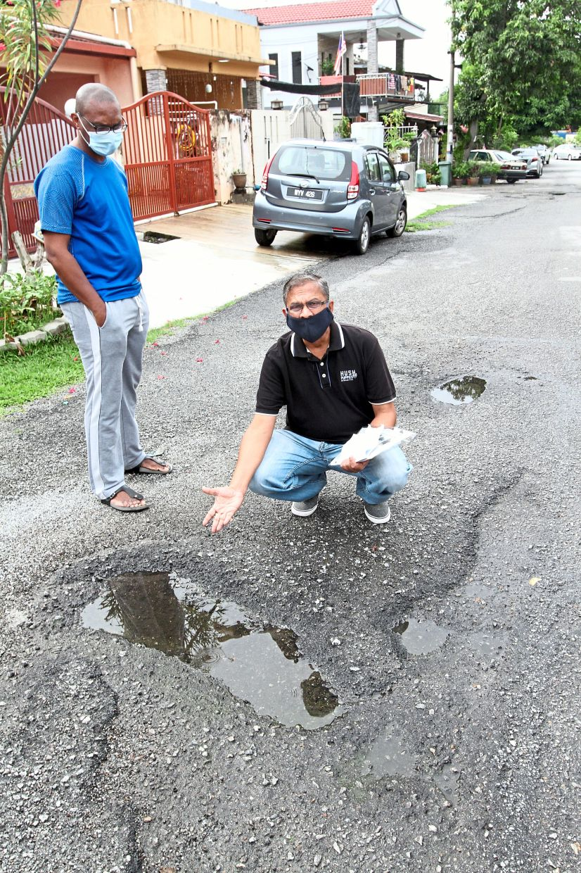 Raj (right) showing one of the potholed roads in Taman Bukit Belimbing. — Photos: LOW BOON TAT/The Star