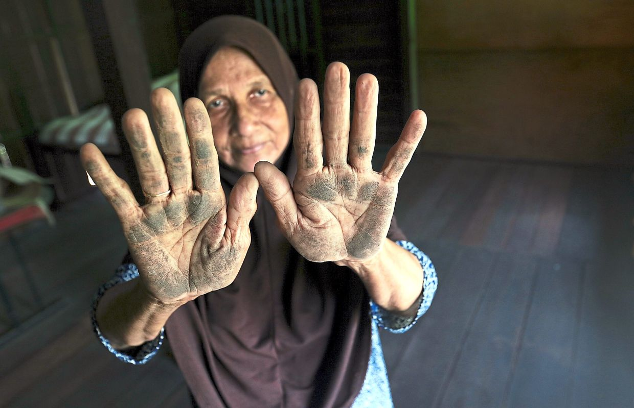 Che Bashah with her palms covered in dust after touching the floor at her house.