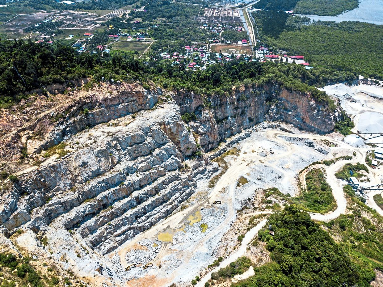 Tall rocky cliffs can be seen after a big portion of the hill was cut off at the granite quarry behind Bukit Juru.