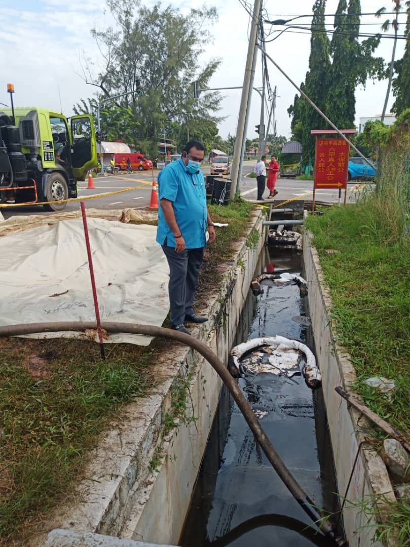Seri Tanjung assemblyman Datuk M. Ravi looking at work being carried out at the scene to contain the spill.