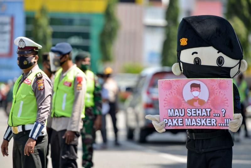 A volunteer wearing a costume holds a placard encouraging people to wear face masks as officials check if motorists are wearing masks adhering to Covid-19 measures in Banda Aceh on Monday (Oct 5). - AFP