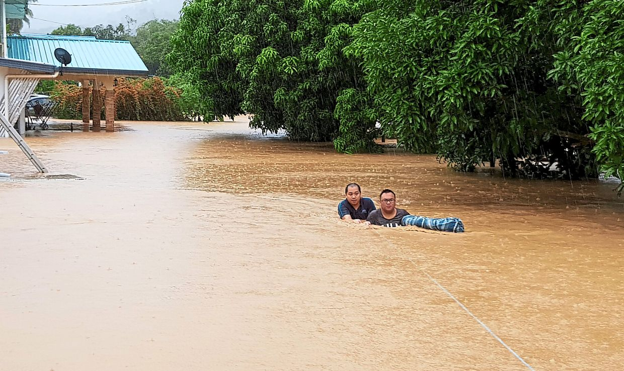 Safety line: A couple of residents from Kampung Kaulan Tamparuli using a rope to wade through the flood waters. (Below) Cars parked in a commercial complex area at Telipok, Kota Kinabalu, partially submerged as water began rising in the early afternoon. — Bernama